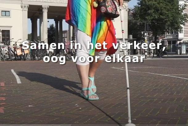 Beeld uit filmpje Oogvereniging: Samen in het verkeer oog voor elkaar: blinde vrouw die straat oversteekt met blindenstok