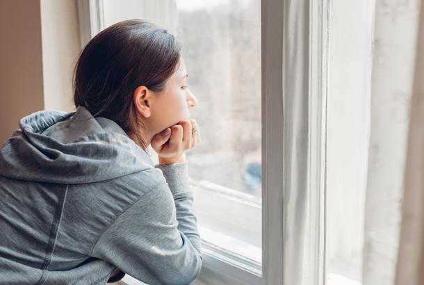 Vrouw in quarantaine kijkt deemoedig vanachter het raam naar buiten