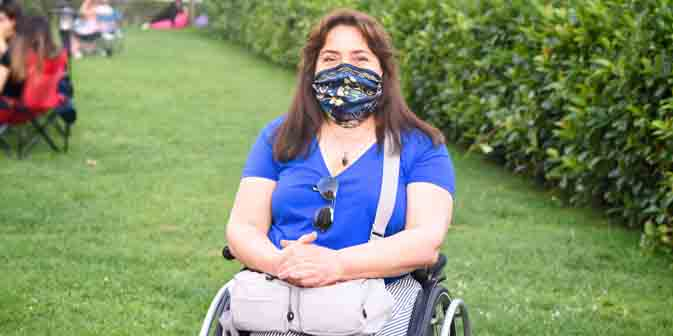 Vrouw buiten in rolstoel met mondkapje