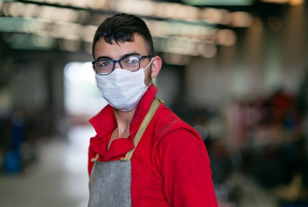 Vriendelijke arbeider met mondkapje op