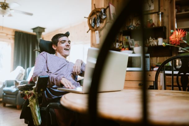 jongen in elektrische rolstoel thuis voor een groot laptopscherm