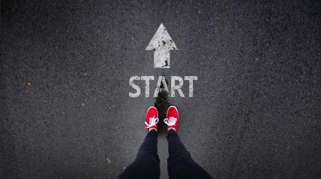 twee voeten in rode gympen staan klaar voor een startpunt op een weg