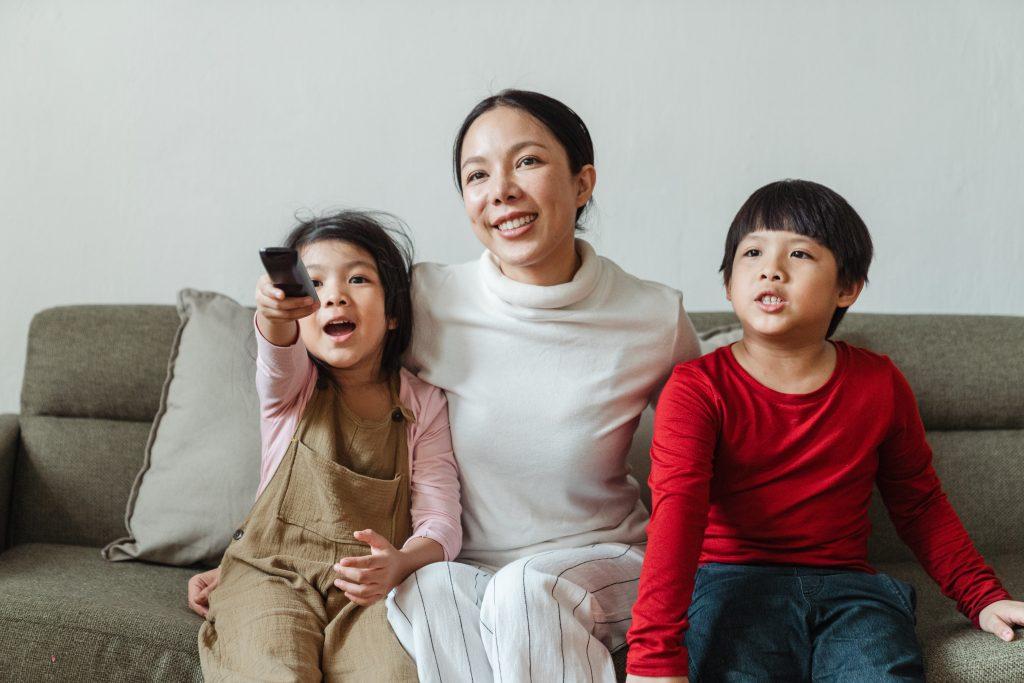Moeder zit op bank met aan elke kant een kind. 1 kindje houdt een afstandsbediening vast. Ze kijken tv.
