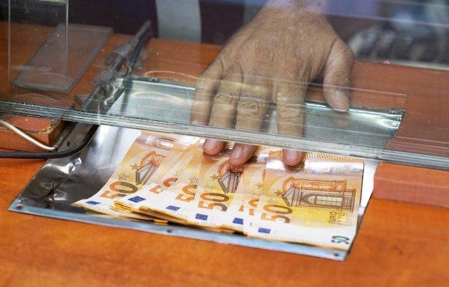 vijftig eurobiljetten worden bij een loket aan klant gegeven