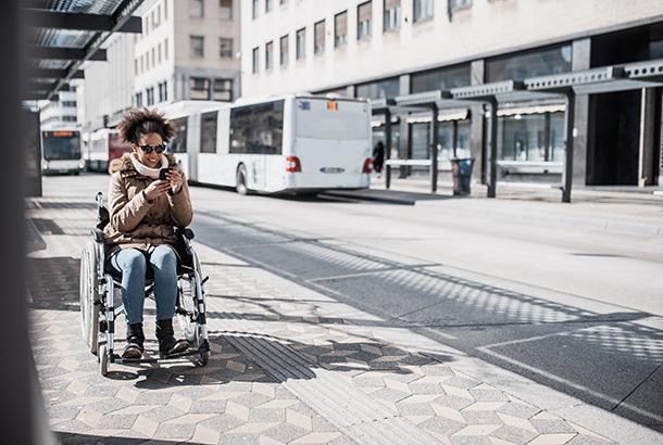 Vrouw in rolstoel wacht op bus en kijkt op haar telefoon