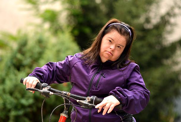 Vrouw met verstandelijke beperking (down) op de fiets